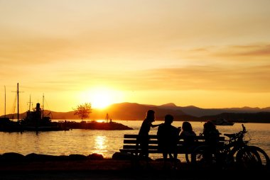 Silhouette of happy family enjoy beautiful sunset view in English Bay