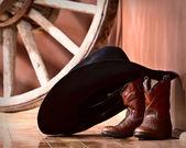 kovbojský klobouk, opíraje se o malé boty