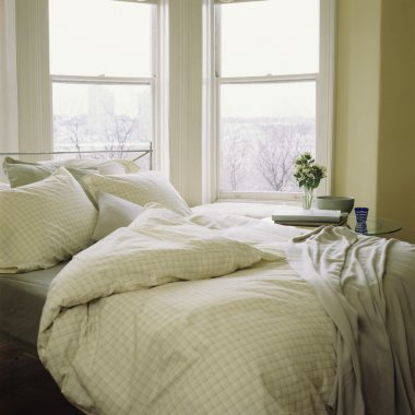 Bed with linens, comforter beside window