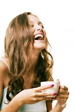 Beautiful laughing girl with a morning cup of tea in his hands