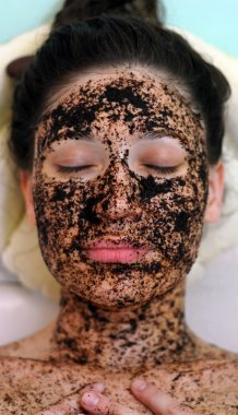 Portrait of a girl with eyes closed in a cosmetic mask of coffee