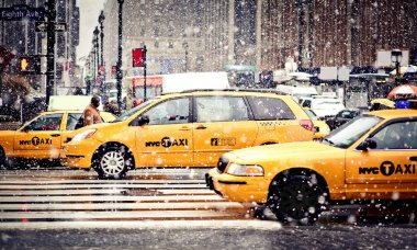 Taxi Cabs cautiously maneuvering through a blizzard