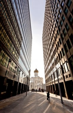 Old russian church between two modern skyscrapers