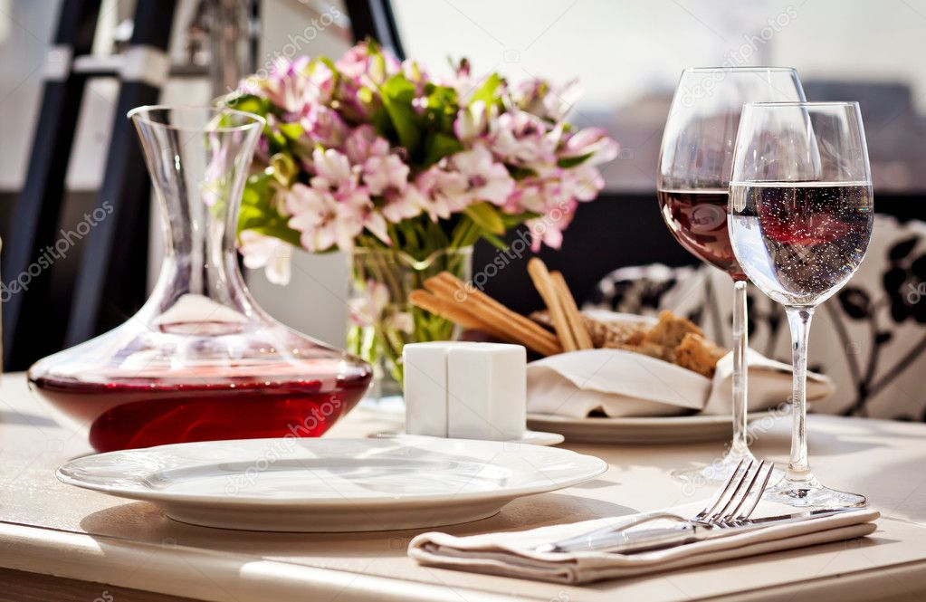 Fine restaurant dinner table place setting: napkin, wineglass, plate, bread and flowers