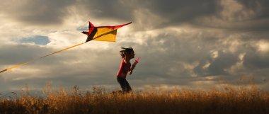 Girl flying a kite.