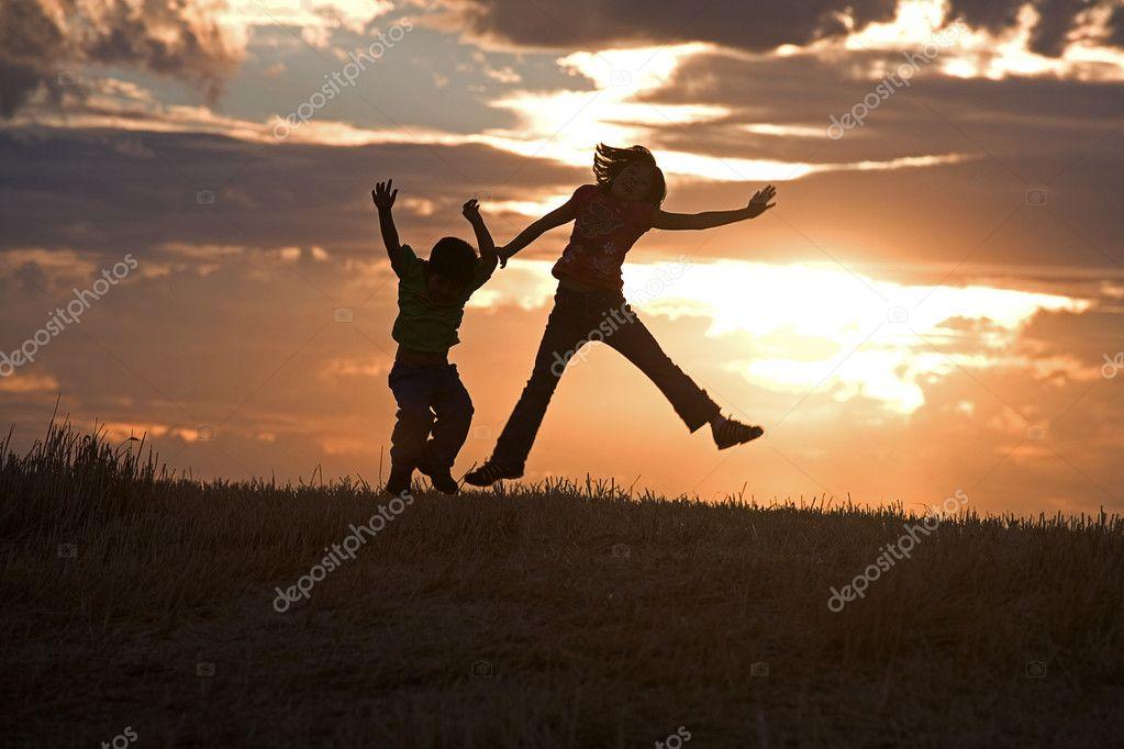 Kids jumping at sunset.