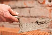 Fotografia muratore posa mattoni per rendere