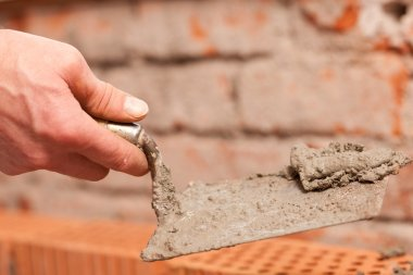Bricklayer laying bricks to make