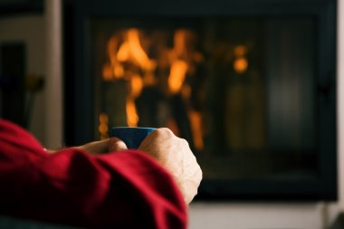 Hot drink in front of fireplace