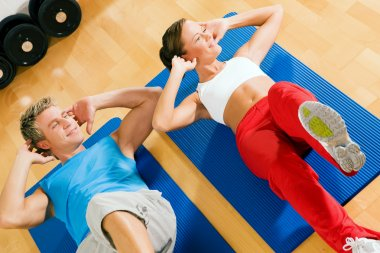 Sportive couple doing sit-ups