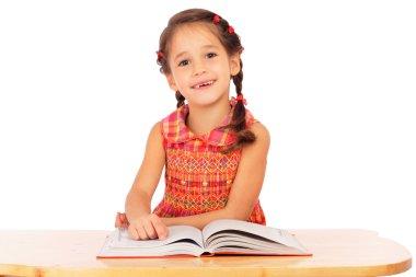 Smiling little girl reading book on the desk