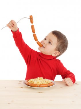 Little boy eating the chain of sausages