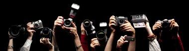 Raised hands holding photocameras