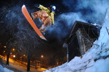 Jumping snowboarder in the city in winter stock vector