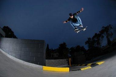 Skateboarder jumping from ledge