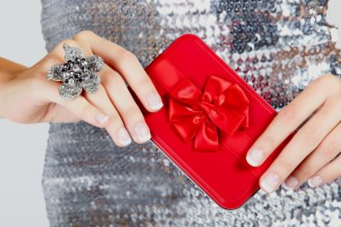 Red gift box in woman's hands.