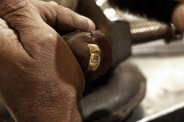 Hardworking Goldsmith working on a gold ring