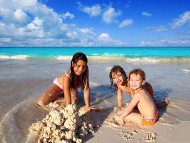 Three little girls mixed ethnicity playing beach