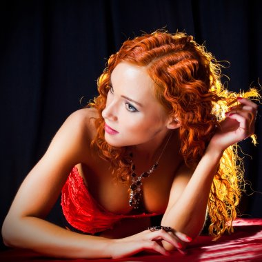 Sexy girl with red hair wearing amber ring and necklace on black