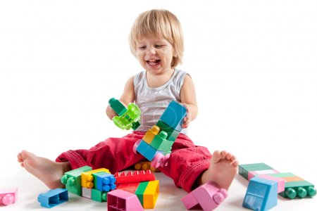 Laughing little boy playing with colorful blocks