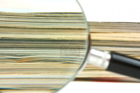 Foto de Magnifying glass and a stack of magazines - Imagen libre de derechos