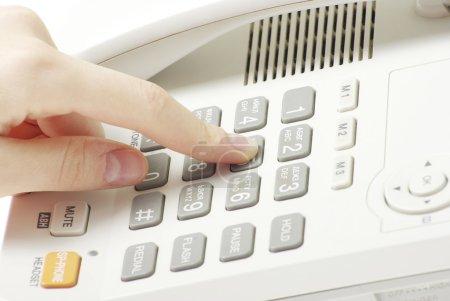 Photo pour Doigt avec clavier téléphonique blanc - image libre de droit