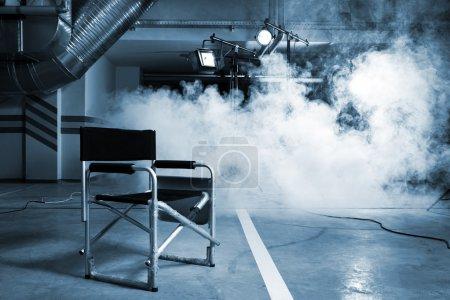 Photo pour Chaise pour le réalisateur en studio sur fond de fumée - image libre de droit