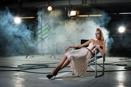Photo pour Jeune fille sur une chaise sous les rayons de projecteurs - image libre de droit