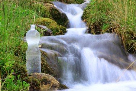 Photo pour Bouteille en plastique avec de l'eau propre sur un fond de ruisseau avec flou de mouvement - image libre de droit