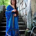 Medieval beautiful girl standing next ancient spri...