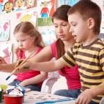 Children painting with teacher in art class.