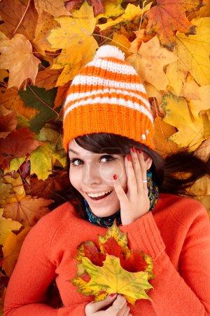 Girl in autumn orange hat on leaves.
