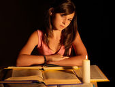 Girl reading book with candle.