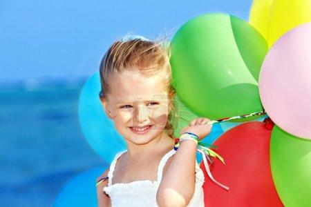 Photo pour Petite fille jouant avec des ballons à la plage. - image libre de droit