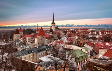 Photo for Overview of Tallinn in Estonia taken from the overlook in Toompea showing the town walls and churches. Taken in HDR to enhance the sunset - Royalty Free Image