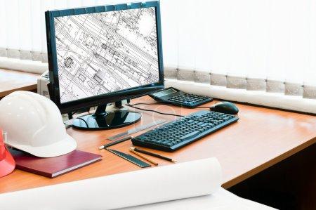 Arbeitsplatz mit Computer, Harthut und Projektzeichnungen. Zeichnung in Angst