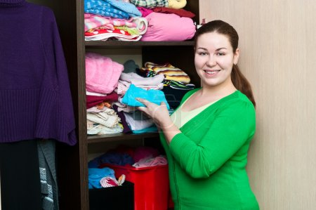 Young caucasian woman in the wardrobe packs things on a shelfs.