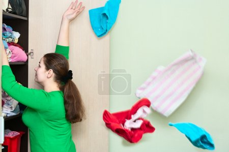 Young caucasian woman throwing a clothes