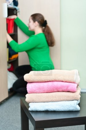 Photo for Stack of clothes and young caucasian woman arranging things in the wardrobe on background. - Royalty Free Image