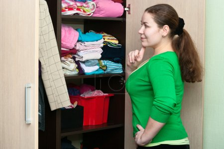 Young woman thinking about to put on near wardrobe