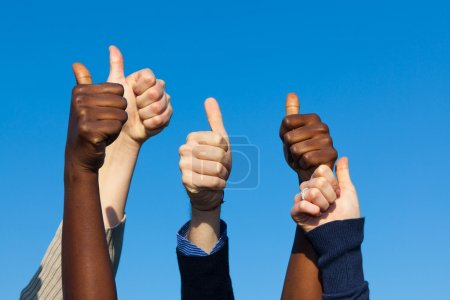Photo for Multiracial Thumbs Up Against Blue Sky - Royalty Free Image