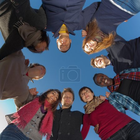 Multiracial Holding Hands in a Circle, Low Angle View