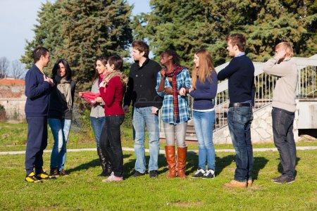 Photo pour Étudiants du collège Marcher et parler au parc - image libre de droit