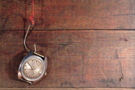 Photo pour Vieille montre suspendue à un hameçon avec fil rouge sur fond en bois - image libre de droit