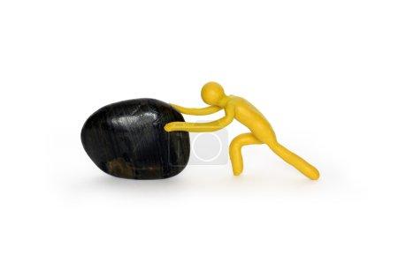 Photo pour Homme en plasticine jaune poussant pierre noire. Isolé sur blanc avec chemin de coupe - image libre de droit