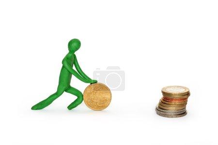 Photo pour Homme de plasticine verte rouler pièce de monnaie à empiler de pièces. Isolé sur blanc avec chemin de coupe - image libre de droit