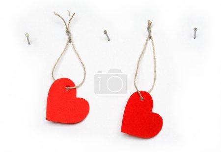 Photo pour Coeurs en papier rouge suspendus sur fond blanc avec corde et clou - image libre de droit
