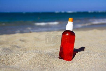 Spray tube with sun protection on beach of ocean