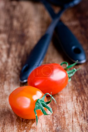 Two fresh tomatoes and kitchen utensil on wooden b...
