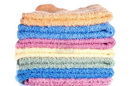 Photo pour Serviettes colorées empilées sur un fond blanc - image libre de droit